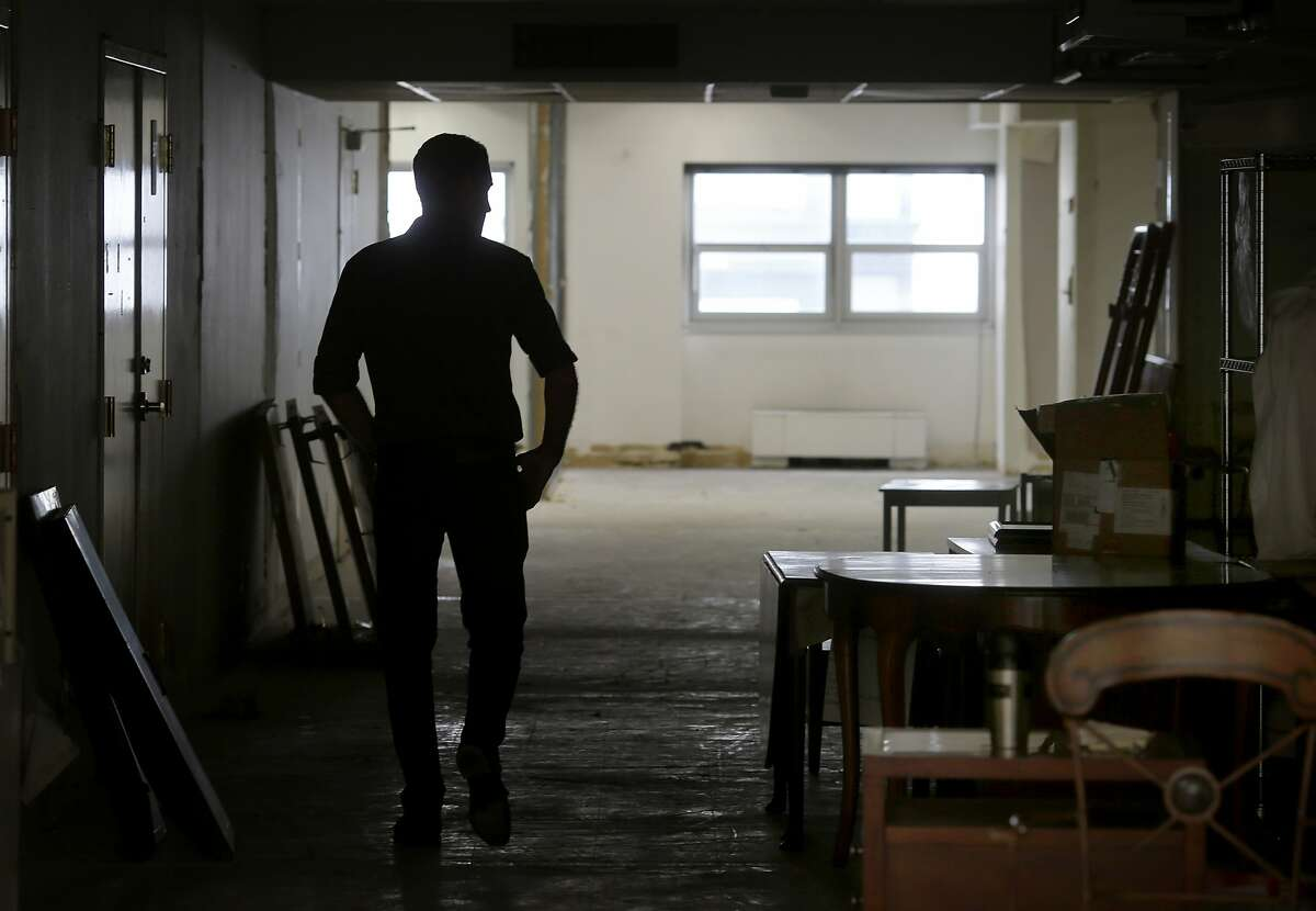 BuildInc Development Manager Joe Peters walks past furniture stored in his building for the Compass Family Services organization Tuesday July 14, 2015. Two buildings and a parking lot near the corner of Van Ness and Market Streets in San Francisco, Calif. may have a date with the wrecking ball, but before they are knocked down it is coming alive as a home for nonprofits and artists.