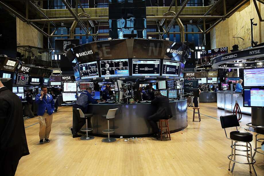 "Traders stand on a nearly empty trading floor at the New York Stock Exchange after trading was halted due to a ""technical glitch"" on July 8, 2015 in New York City. Some traders on the floor said it was hard to get information about the nature of the problem and how long it would take to fix. Senior workers who had served as the go-between with traders during past disruptions were let go over the last year. Photo: Spencer Platt, Getty Images"