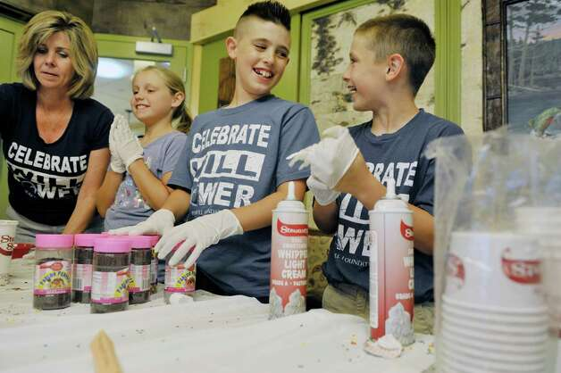 Mary Grasso, left, Lily Haluska, second from left, 9, Ben Hladun, third from left, 11, and Luke Haluska, 10 serve up ice cream toppings during an ice cream social put on by the Brave Will Foundation at the Bernard & Millie Duker Children's Hospital at Albany Med on Tuesday, July 14, 2015, in Albany, N.Y.  Ben's brother, Will Hladun, died in 2009 at six months old from a rare form of cancer, and every year the foundation hosts the ice cream social with volunteers from the foundation serving up ice cream.   (Paul Buckowski / Times Union) Photo: PAUL BUCKOWSKI / 00032603A