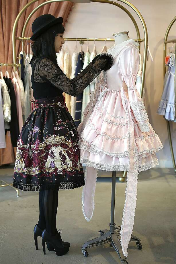 "At Baby the Stars Shine Bright boutique in S.F., sales associate Aki Haseqawa  wears the Electric Circus in the Moonlight Night skirt from Alice and the Pirates as she places a ""Cinderella"" one-piece dress on a mannequin. Baby the Stars Shine Bright is located in the New People building in San Francisco's Japantown. Photo: Liz Hafalia, The Chronicle"