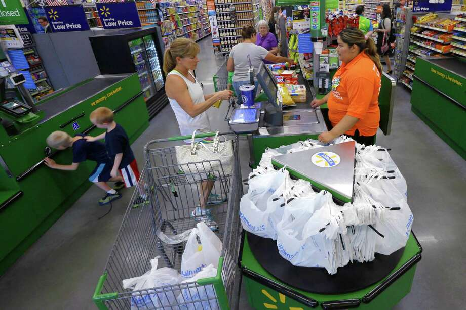 In this June 4, 2015 photo, a customer, center, checks out at a Wal-Mart Neighborhood Market store in Bentonville, Ark. The Commerce Department releases retail sales data for June on Tuesday, July 14, 2015. (AP Photo/Danny Johnston) Photo: Danny Johnston, STF / Associated Press / AP