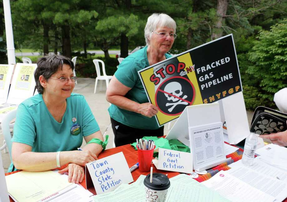 (Left) Sharon Johnson, 65, of Schodack, and Jane Roberts, 72, of Stephentown sell signs and present petitions to protesters outside the public meeting held by the Federal Energy Regulatory Commission about the Northeast Energy Direct natural gas pipeline project on Tuesday, July 14, 2015, in Castleton-on-Hudson, N.Y. (Olivia Nadel/ Special to the Times Union) Photo: ON / 00032605A