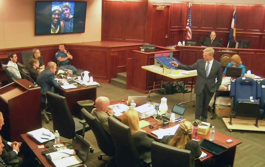 In this image taken from video, accused Colorado theater shooter James Holmes, left, listens to lead prosecutor George Brauchler give closing arguments during his trial, in Centennial, Colo., Tuesday, July 14, 2015. On the screen is a photo of Alexander J. Boik, 18, who had just graduated from high school in Aurora. With him is his girlfriend, Lasamoa Cross, who testified that the couple snapped a photo of themselves just before the show started, with Boik wrapping his arm around her shoulders. She was uninjured. (Colorado Judicial Department via AP, Pool) ORG XMIT: COLO101 / POOL Colorado Judicial Department