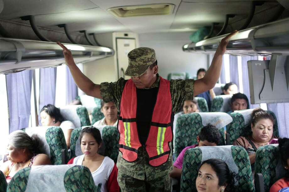 "A soldier inspects a bus at a checkpoint on the highway connecting Mexico City and Acapulco, in Guerrero State, Mexico, on July 14, 2015. Mexico's government offered a $3.8 million reward for the capture of fugitive drug lord Joaquin ""El Chapo"" Guzman on Monday and sacked top prison officials amid suspicions that guards helped him escape. Guzman vanished from his cell late Saturday even though he was wearing a monitoring bracelet and surveillance cameras were trained on the room 24 hours a day, Interior Minister Miguel Angel Osorio Chong said.  AFP PHOTO / PEDRO PARDOPedro PARDO/AFP/Getty Images Photo: PEDRO PARDO, Stringer / AFP / Getty Images / AFP"