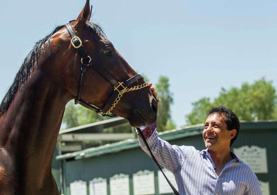 Jockey Victor Espinoza greets Triple Crown winner American Pharoah after the horse arrived at Santa Anita Park in Arcadia, Calif., Thursday, June 18, 2015. (AP Photo/Ringo H.W. Chiu) ORG XMIT: CARC108 Photo: Ringo H.W. Chiu / FR170512 AP