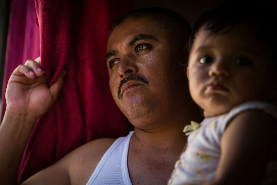 Jaime Ortiz stares out a window while holding his baby daughter, Leslie Ortiz, at the Prentice Apartments in Healdsburg. They will be forced to move because of a rent increase. Photo: Loren Elliott, The Chronicle