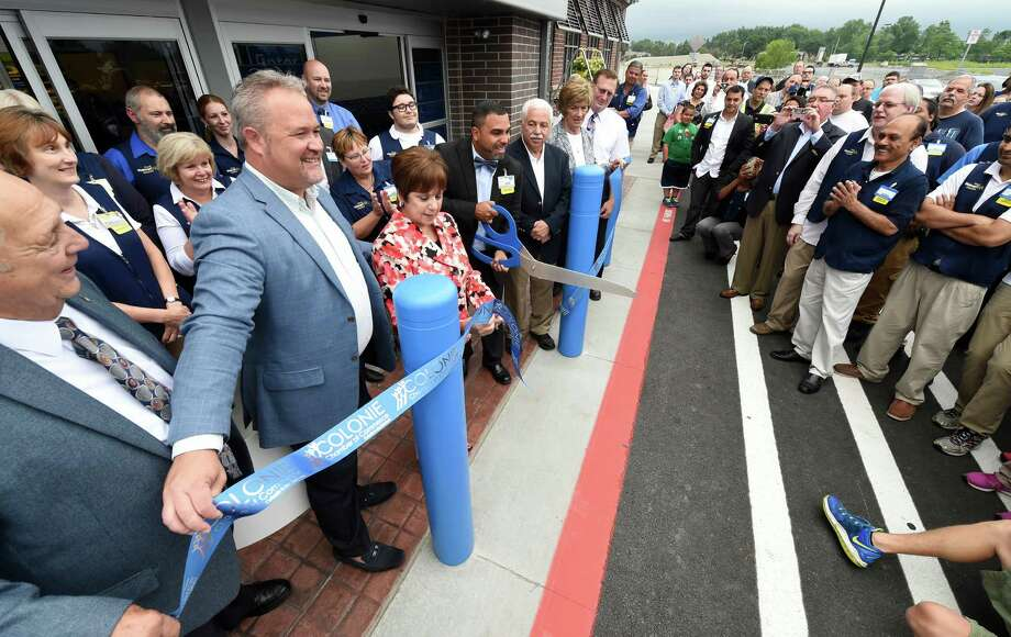 Colonie Town Supervisor Paula Mahan, third from left, assists store manager Juan Rivera as they cut the ribbon July 15, 2015, at the opening ceremonies of the new Walmart in the Shoppes at Latham Circle in Colonie, N.Y.     (Skip Dickstein/Times Union) Photo: SKIP DICKSTEIN / 00032573A