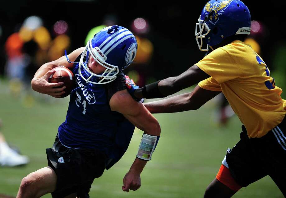 Darien's Shelby Grant makes a catch in front of a Harding defender during the annual Grip It and Rip It 7-on-7 passing tournament at New Canaan High School on Saturday. Photo: Autumn Driscoll / Hearst Connecticut Media / Connecticut Post