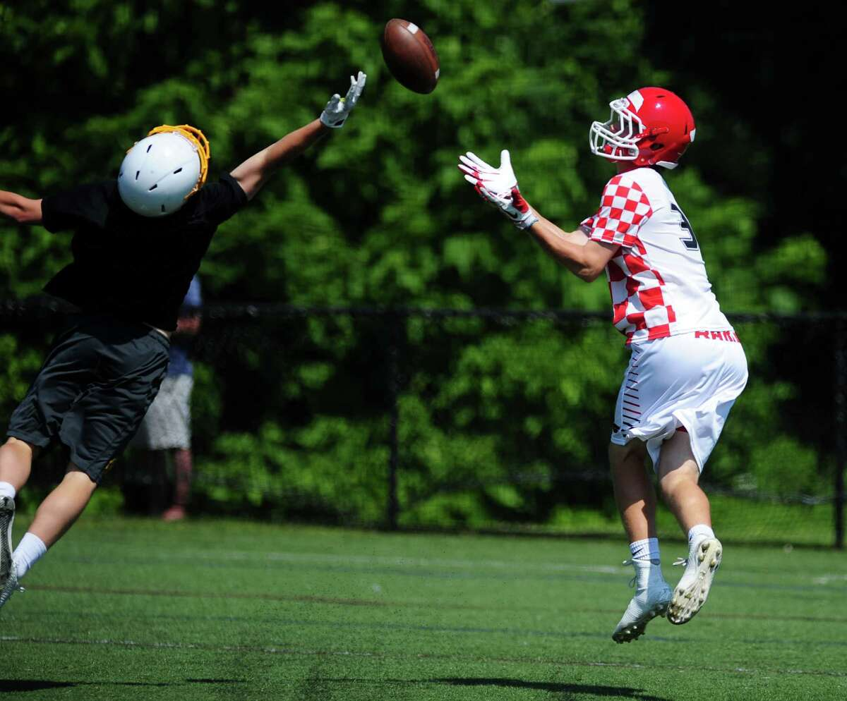 New Canaan High School's Peter Swindell, right, catches a pass during the annual Grip It and Rip It 7-on-7 passing tournament at New Canaan High School Saturday, July 11, 2015.