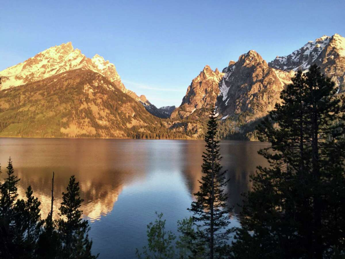 Alpenglow shining on the Grand Tetons is reflected in Jenny Lake June 4, 2015, in Grand Teton National Park, Wyoming. Three men, including Drew McCord of Houston, were rescued from Granite Canyon early Christmas morning. (Erin Madison/Great Falls Tribune via AP) Click through the slideshow to learn how some people have died inside of Texas state parks