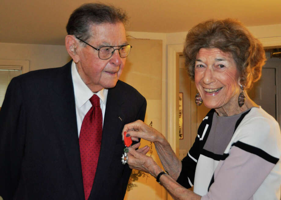 Ted Diamond has the Legion of Honor medal pinned onto his jacket by Carol Diamond, his wife of 69 years. Photo: Contributed / Contributed Photo / Westport News