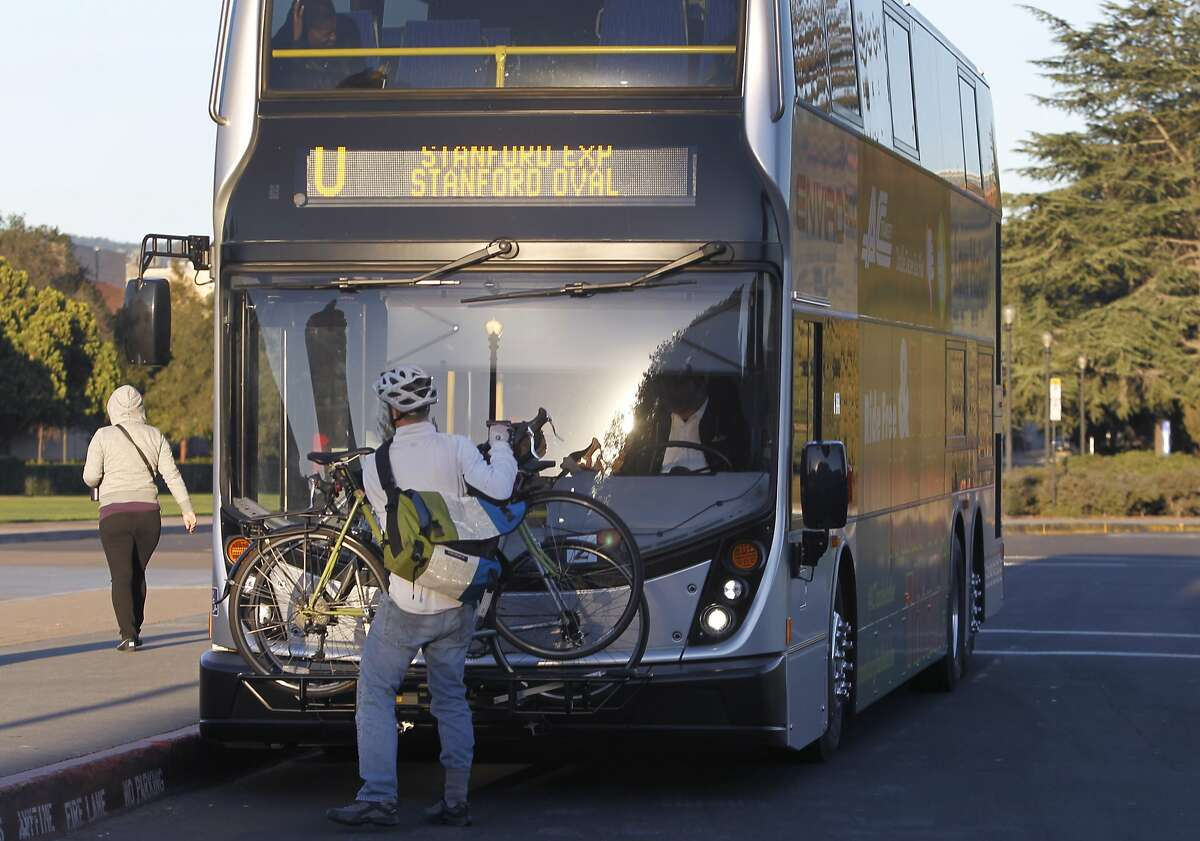 A man removes his bicycle at Stanford University after commuting from Fremont, Calif. on Tuesday, Feb. 24, 2015. AC Transit tested the 80-seat double-decker buses to meet growing ridership demand.
