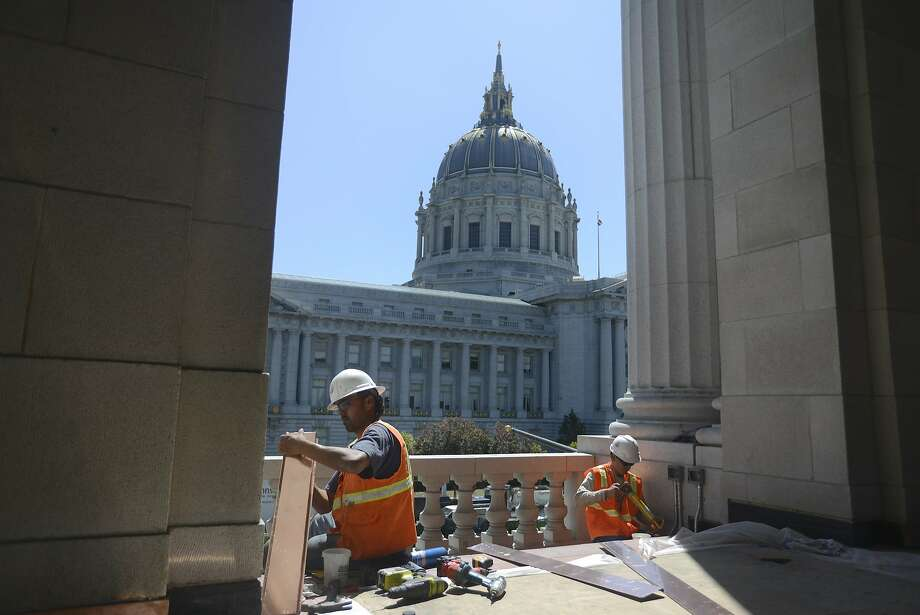 Cesar Aguilera (left) and Angel Corodoso (right) fit copper plating trim to the outside of the San Francisco War Memorial and Performing Arts Center in San Francisco, California, on Wednesday, July 15, 2015. Photo: Brandon Chew, The Chronicle