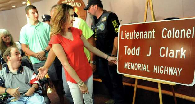 Shelley Clark of San Antonio, Texas, center, wife of Lt. Col. Todd J. Clark, touches the sign to rename a portion of Route 146 in his honor during a dedication ceremony on Wednesday, July 15, 2015, at Guilderland Town Hall in Guilderland, N.Y. (Cindy Schultz / Times Union) Photo: Cindy Schultz / 00032642A
