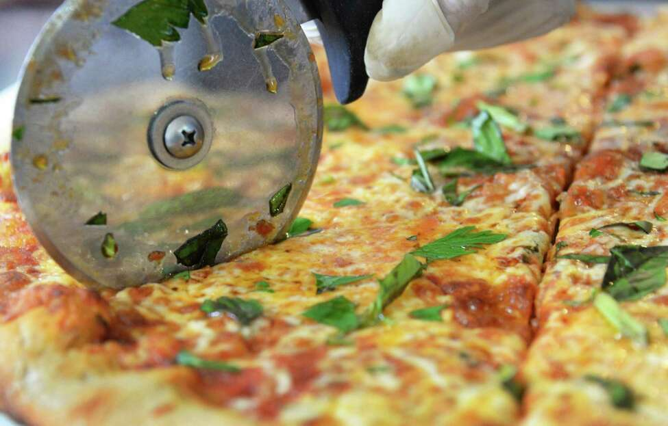 Slicing a farmhouse pizza just out of the oven at 9 Miles East Farm Wednesday July 8, 2015 in Schuylerville, NY. (John Carl D'Annibale / Times Union)