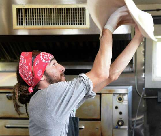Pizza baker Matthew Geiling tosses pizza dough in the kitchen at 9 Miles East Farm Wednesday July 8, 2015 in Schuylerville, NY.  (John Carl D'Annibale / Times Union) Photo: John Carl D'Annibale / 00032515A