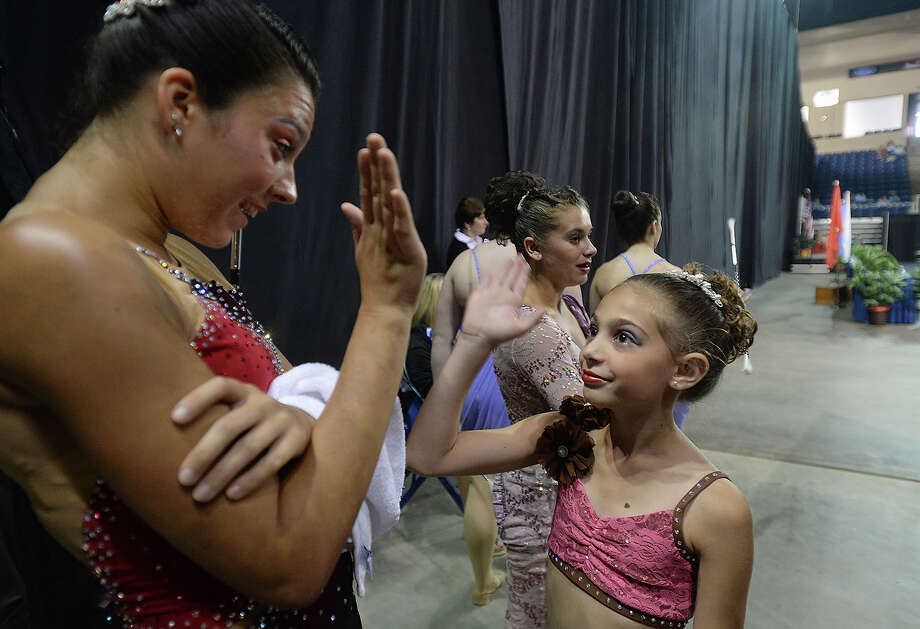 Long Island's Victoria Massey high-fives Antoinette Sena, 11, before they get ready for their respective competitions in the wings at the U.S. National Baton Twirling Championships Tuesday at Ford Park. The week-long event features top twirlers from across the country competing in a variety of traditional, artistic and dance events. Wednesday's finals are free and open to the public. Additional team and twirling spectator events continue through Saturday. Photo taken Tuesday, July 14, 2015 Kim Brent/The Enterprise Photo: Kim Brent / Beaumont Enterprise
