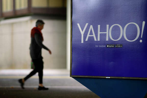 A pedestrian walks under the Rockridge BART Station in Oakland, passing one of the Yahoo ads promoting its mobile services.
