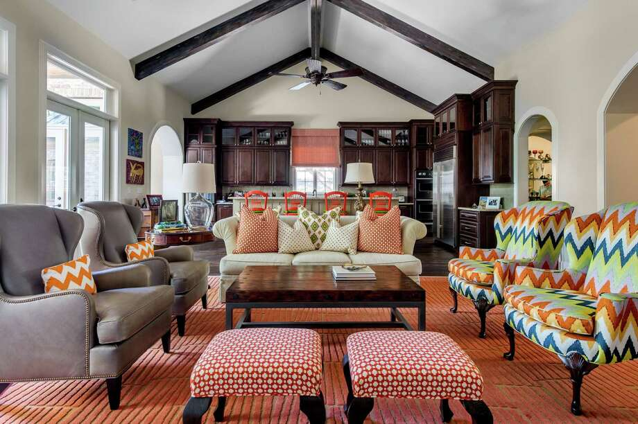 The Tellers' living room and open kitchen have high ceilings and bright color, from the patterned wing chairs to the glossy orange bar stools. Photo: Blake Mistich