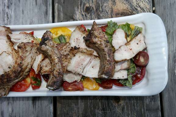 The finished pork chop dish is presented on a bed of homegrown tomatoes Tuesday July 14, 2015. Chef Taylor Boetticher of Fatted Calf prepares pork chops al'diavolo at his home in hills above Sonoma, Calif.