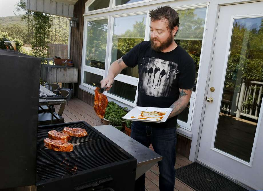 Taylor Boetticher throws the pork chops on the flame after marinating them Tuesday July 14, 2015. Chef Taylor Boetticher of Fatted Calf prepares pork chops al'diavolo at his home in hills above Sonoma, Calif. Photo: Brant Ward, The Chronicle