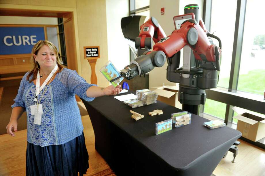 Lynn DeRose, a GE scientist that is part of the company's software and analytics group at the GE Global Research Center, accepts a package from Baxter, a collaborative robot made by Rethink Robotic, as DeRose gave a demonstration of the robot at the 2015 Industrial Internet Summer Conference at the GE Global Research Center on Wednesday, July 15, 2015, in Niskayuna, N.Y.  The robot through sensors can work interactively with people say on a production line.   (Paul Buckowski / Times Union) Photo: PAUL BUCKOWSKI / 00032615A
