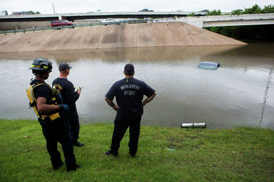 The Houston Fire Department checks a flooded car on the frontage road in between South Loop West Freeway and South Post Oak Road near the Willow Waterhole Bayou, Tuesday, May 26, 2015, in Houston. ( Marie D. De Jesus / Houston Chronicle ) Photo: Marie D. De Jesus, Staff / © 2000 Houston Chronicle