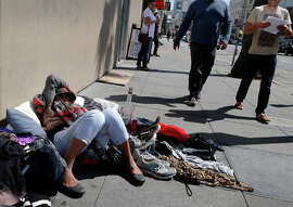 Above, a woman slept near the corner of Mission and Sixth streets as she displayed clothing for sale.