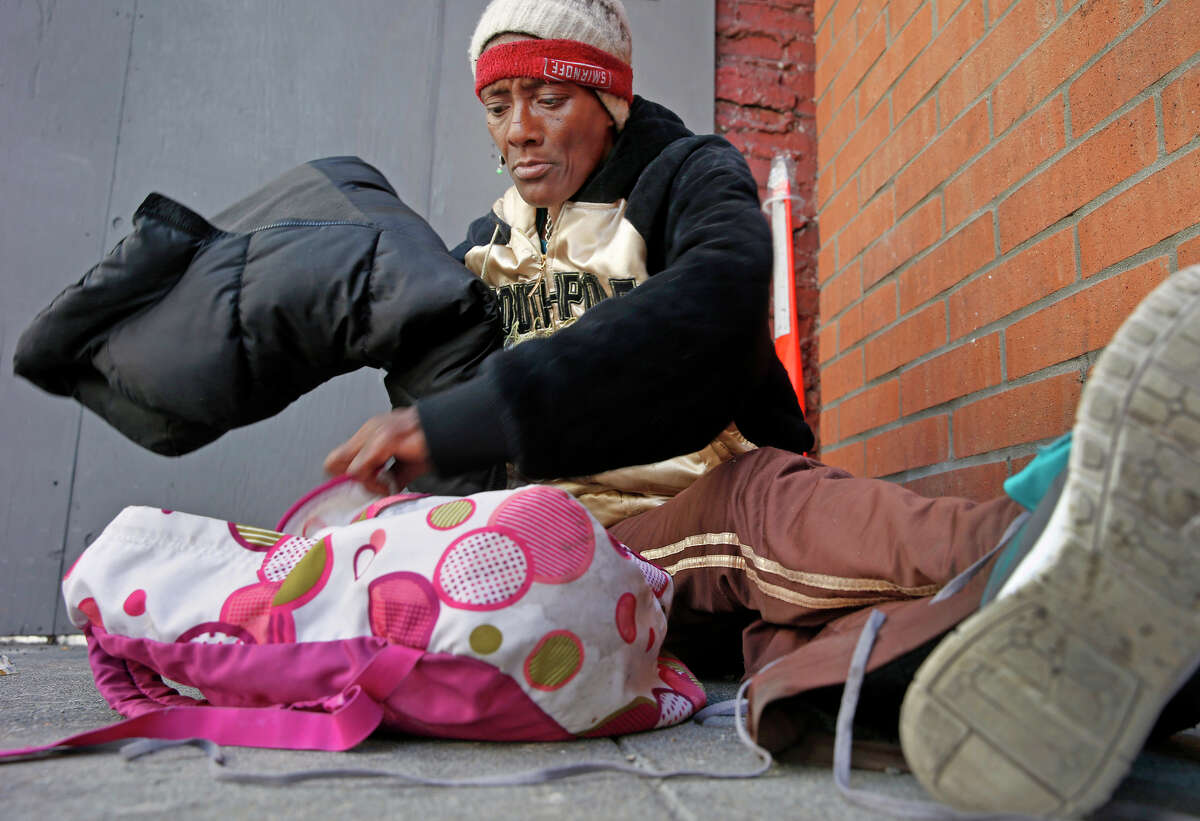 A homeless woman named Listern gets her belongings together as she sits on O'Farrell Street near Union Square.
