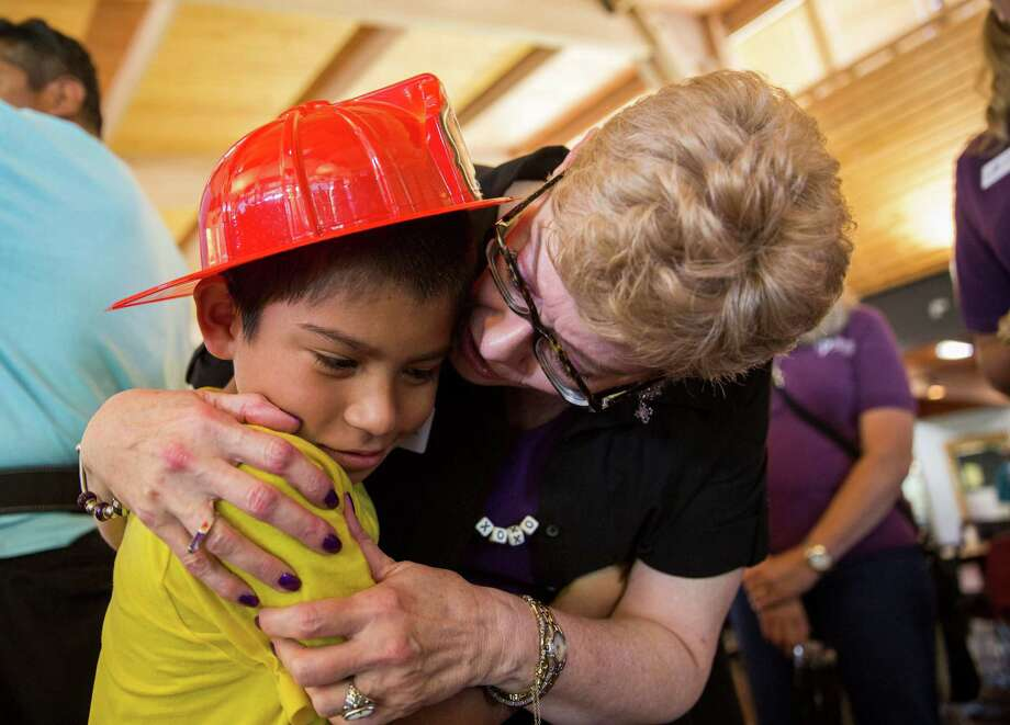 "Jose Ovalle gets a hug from Sue Dodson, executive director of the Texas Burn Survivor Society. To campers at Camp David, she's known affectionately as ""Miss Sue."" Photo: Ray Whitehouse / San Antonio Express-News / 2015 San Antonio Express-News"