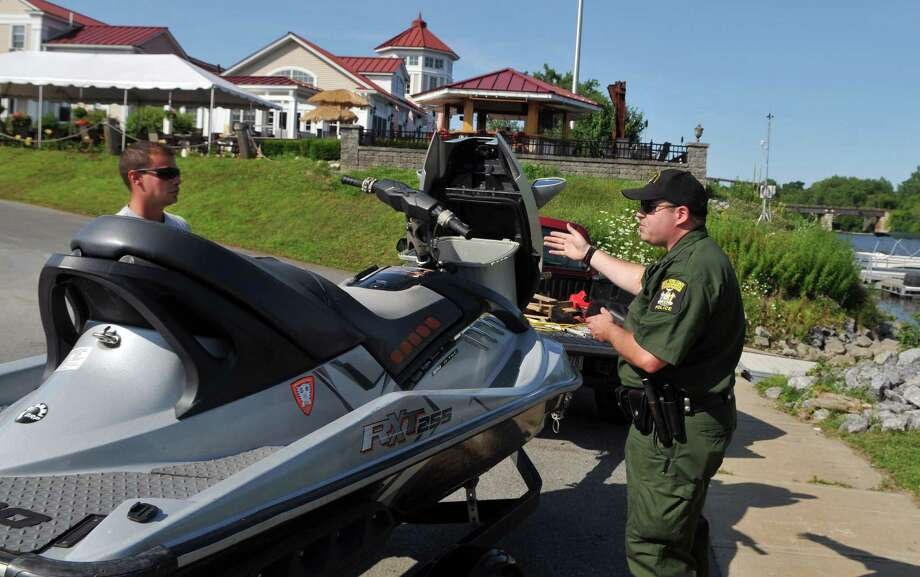 Lieutenant James Hays Jr., right, examines Schenectady resident Jason Kriss's jet ski for any invasive species as part of DEC's Invasive Species Awareness Week Wednesday, July 15, 2015, at the Freemans Bridge Road Boat Launch in Glenville, N.Y. (Phoebe Sheehan/Special to The Times Union) Photo: PS / 00032602A