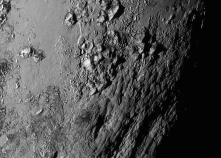 This Tuesday, July 14, 2015 image provided by NASA on Wednesday shows a region near Pluto's equator with a range of mountains captured by the New Horizons spacecraft. (NASA/JHUAPL/SwRI via AP) ORG XMIT: NY129 / NASA/JHUAPL/SwRI