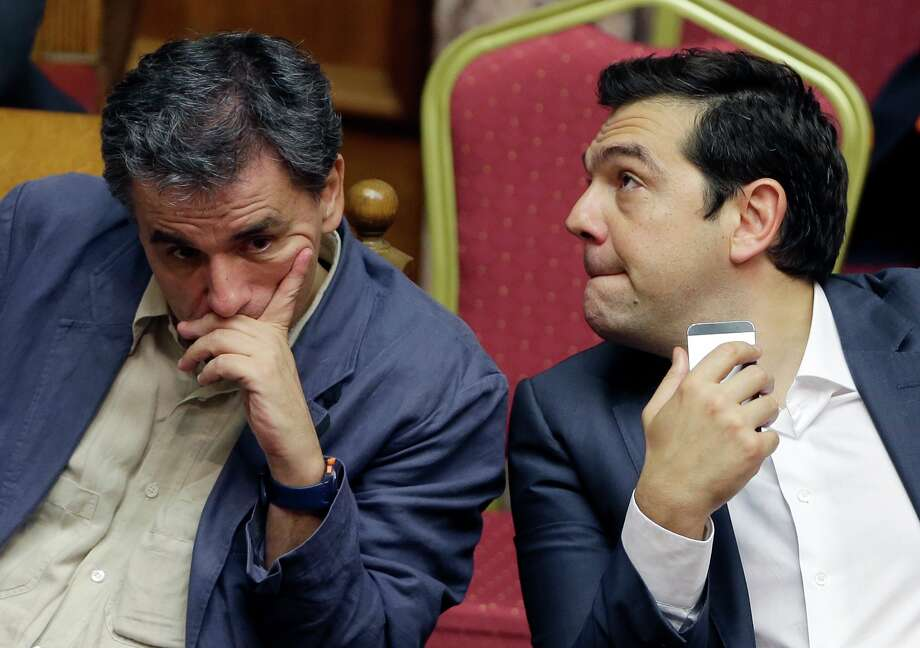 Greece's Prime Minister Alexis Tsipras, right, and Finance Minister Euclid Tsakalotos react as they attend a parliament meeting in Athens, Thursday, July 16, 2015. Greece's Parliament has approved an austerity bill demanded by bailout creditors, despite a significant level of dissent from the governing leftist Syriza party. The bill to impose sweeping tax hikes and spending cuts was approved with the support of three pro-European opposition parties. (AP Photo/Thanassis Stavrakis) ORG XMIT: XTS115 Photo: Thanassis Stavrakis / AP
