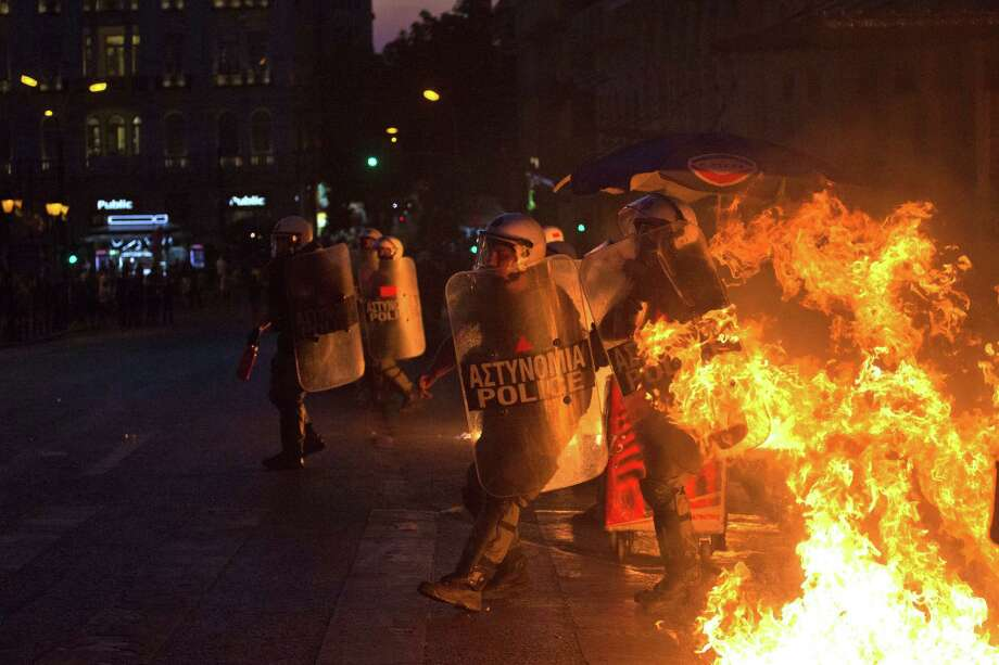 Riot police back away from fires started as anti-austerity protesters throw gasoline bombs during clashes in Athens on Wednesday. Photo: Emilio Morenatti / Associated Press / AP