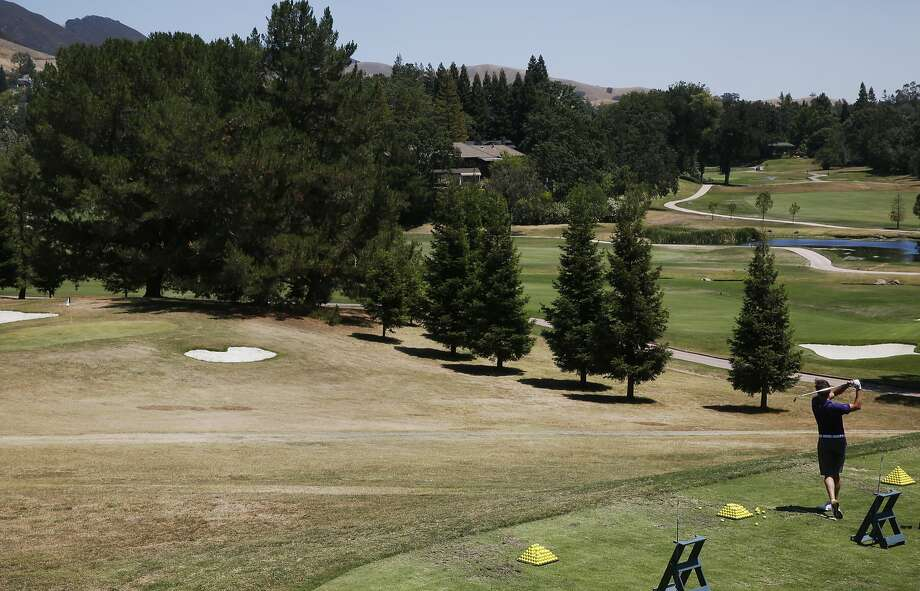 Scott Clark takes a shot at the practice range at the Diablo Country Club July 15, 2015 in Diablo, Calif. The club has cut back on their irrigation by 35-40 percent, leaving swaths of brown grass throughout the course. Photo: Leah Millis, The Chronicle