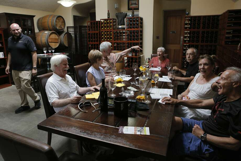 A group of vacationers visits the Williamson Wines tasting room in downtown Healdsburg. As the town becomes more popular as a vacation destination, prices have risen dramatically and many longtime residents are being priced out. Photo: Loren Elliott, The Chronicle