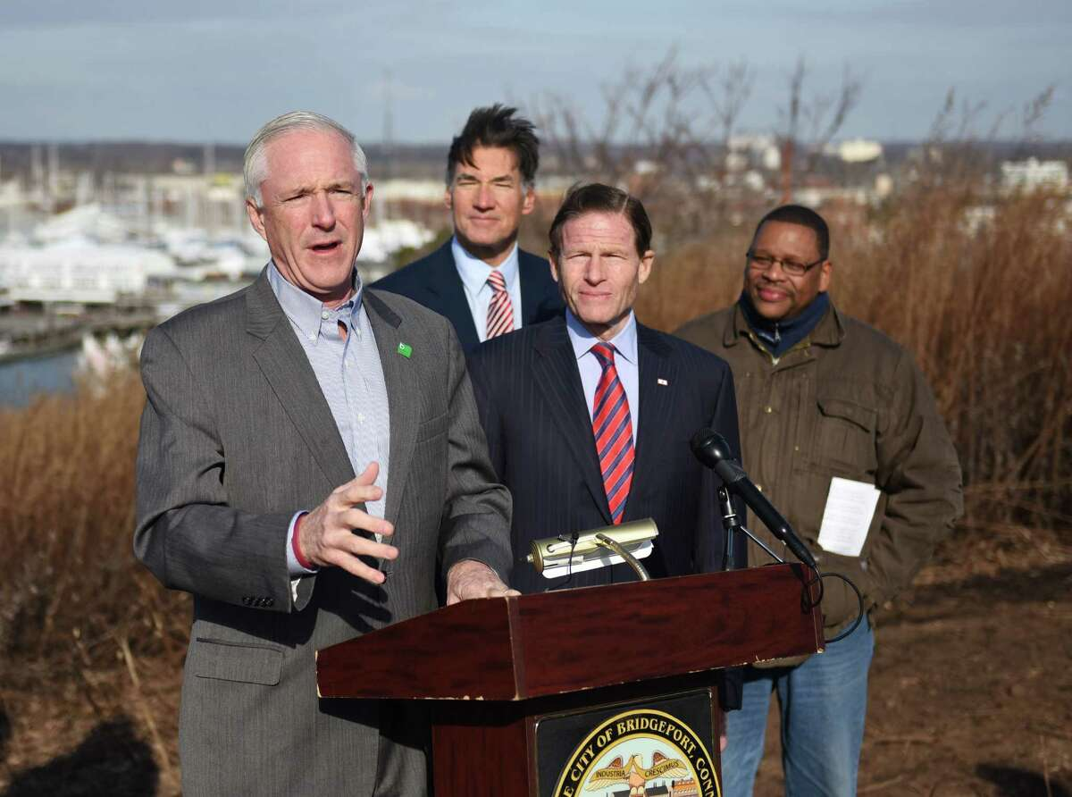 Bridgeport Mayor Bill Finch, left, speaks at the podium beside U.S. Sen. Richard Blumenthal and other officials involved in the project at the future site of the Bridgeport Clean Energy Park in Bridgeport, Conn. Friday, Jan. 2, 2015. The site, at an unused landfill near Seaside Park, will include 9,000 solar panels and a 2.8MW fuel cell to generate clean solar energy powering 5,000 homes. The Green Energy Park project is being overseen by United Illuminating and received recent approval from the Connecticut Siting Council. The ground breaking of the park, which will create 92 new jobs, will be within a month.