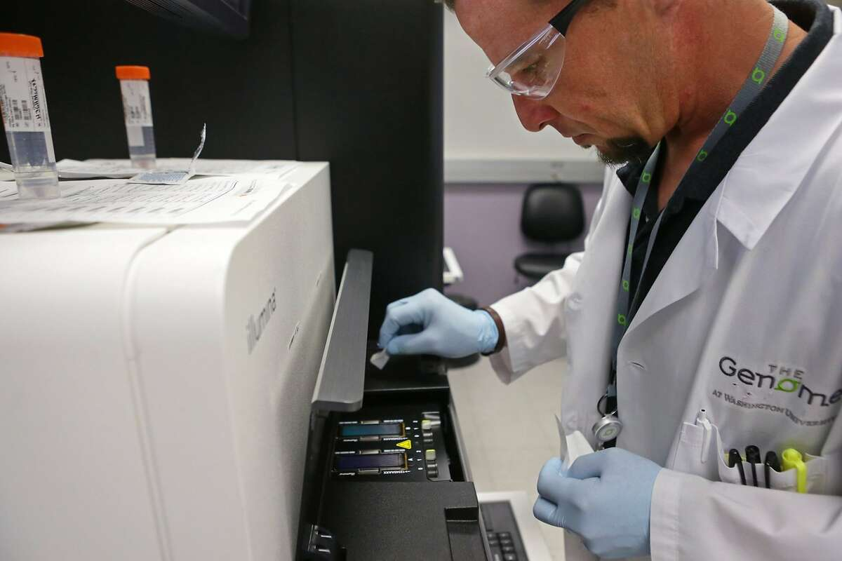 John D'Albora, 41, a senior research technician, wipes impurities from a flow cell before running it through a HiSeq X Ten machine for sequencing at the Genome Institute at Washington University on Thursday, April 23, 2015. (Cristina Fletes-Boutte/St. Louis Post-Dispatch/TNS)