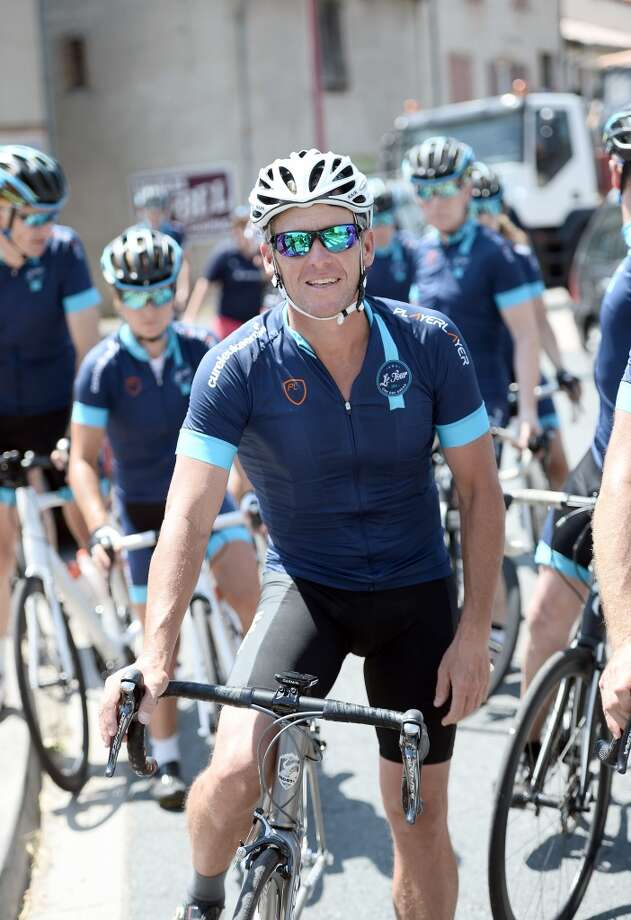 "US cyclist Lance Armstrong waits with his bicycle in Villefranche-d'Albigeois, southwest France, where he stopped for lunch during as he rides a stage of The Tour De France for a leukaemia charity, a day ahead of the competing riders, on July 16, 2015. For the first time since he was stripped of his seven Tour de France titles, disgraced cyclist Lance Armstrong rode a stage of the famous race for charity. Armstrong, 43,  was riding a 198-kilometre (123-mile) stage a day ahead of the competing riders for a leukaemia charity but cycling officials have branded the exercise ""disrespectful."" Photo: STEPHANE DE SAKUTIN, AFP/Getty Images"