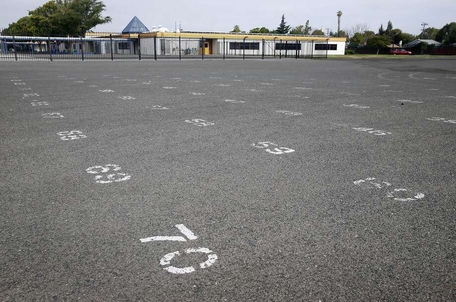 Numbers are painted on a school yard at Madison Park Business and Art Academy in Oakland, Calif. on Thursday, July 16, 2015. Construction is scheduled to start soon on a high school located on what is now a sprawling asphalt playground between the elementary and middle school (background) already on the campus. Photo: Paul Chinn, The Chronicle
