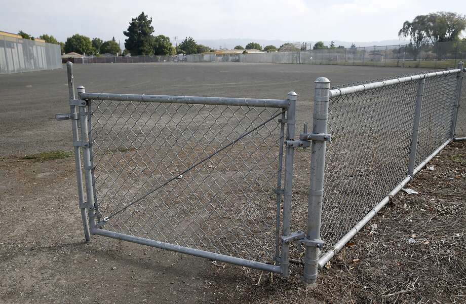 An open gate leads to a school yard from the athletic field at Madison Park Business and Art Academy in Oakland, Calif. on Thursday, July 16, 2015. Construction is scheduled to start soon on a high school located on what is now a sprawling asphalt playground between the elementary and middle schools already on the campus. Photo: Paul Chinn, The Chronicle