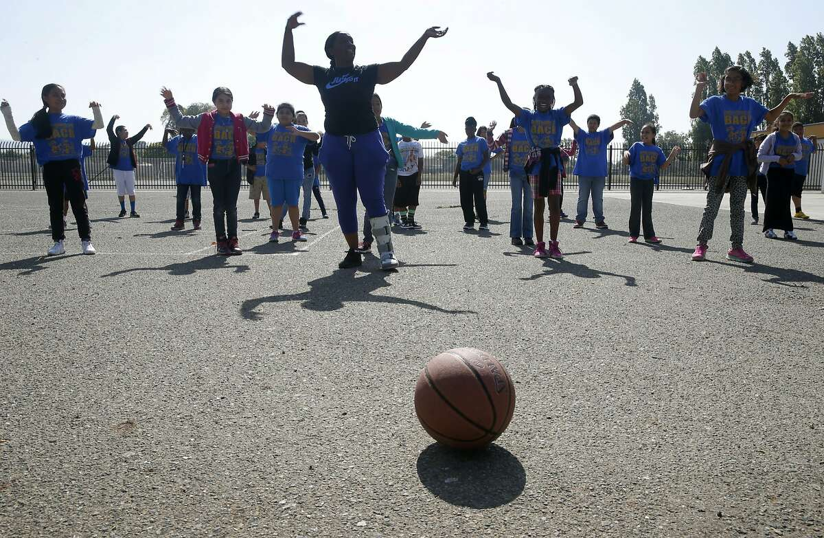Saadiqah Raashid leads summer school students through a series of exercises at Madison Park Business and Art Academy in Oakland, Calif. on Thursday, July 16, 2015. Construction is scheduled to start soon on a high school located on what is now a sprawling asphalt playground (background) between the elementary and middle schools already on the campus.