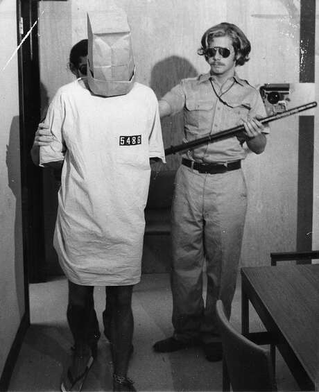 A prisoner, forced to wear a bag over his head, stands with guard John Loftus during the Stanford Prison Experiment. Photo: Duke Downey, The Chronicle
