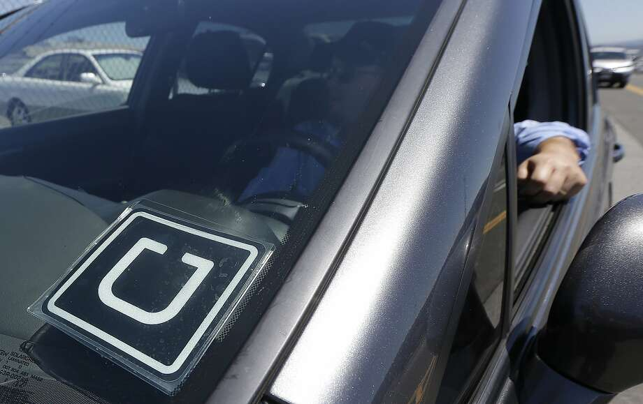 Uber driver Karim Amrani sits in his car parked near the San Francisco International Airport parking area in San Francisco, Wednesday, July 15, 2015. In the three months ended in June, Uber overtook taxis as the most expensed form of ground transportation, according to expense management system provider Certify. (AP Photo/Jeff Chiu) Photo: Jeff Chiu, Associated Press