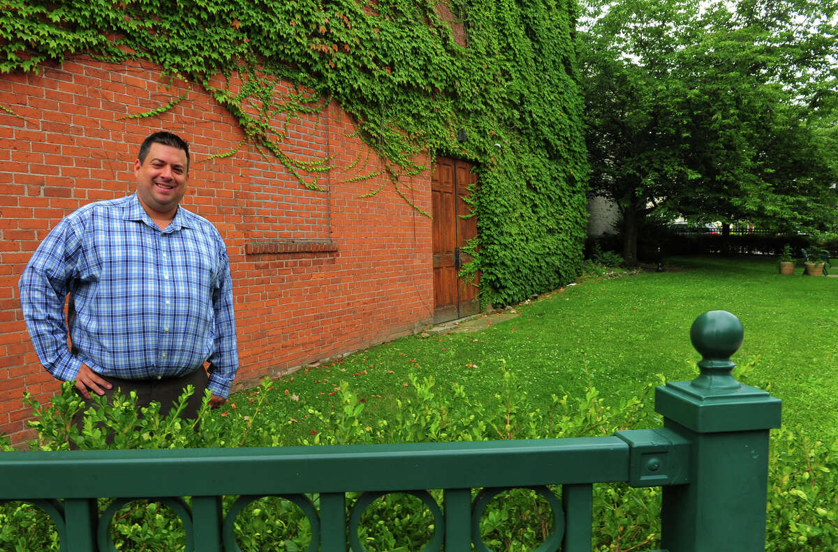 Eli's Tavern General Manager Kevin Fitzsimmons, poses along the side of the restaurant in a small piece of city owned land on Daniel Street in Milford, Conn., on Wednesday July 15, 2015. Fitzsimmons is trying to get permission from the city to use the space for outdoor seating.