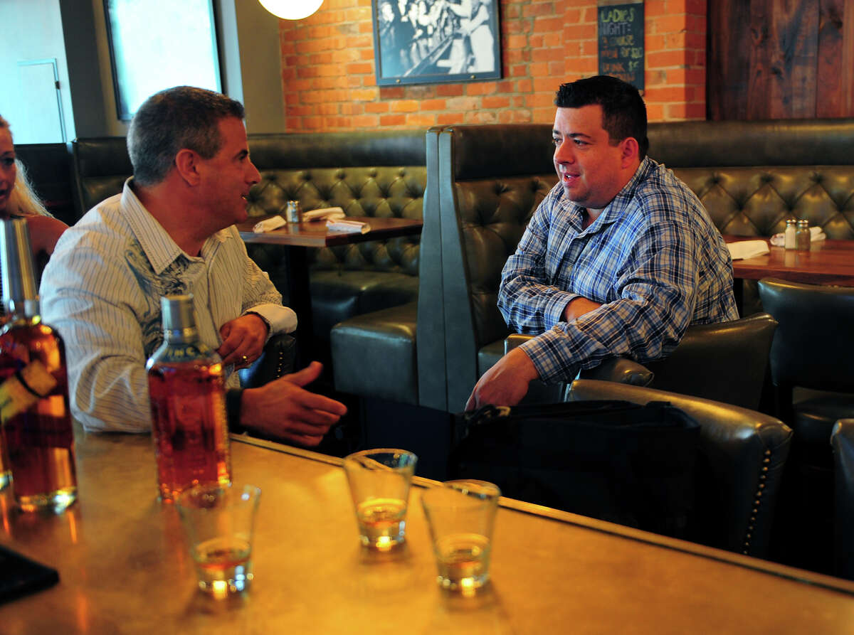 Eli's Tavern General Manager Kevin Fitzsimmons, right, chats with Proximo Spirits sales rep Ray Cruciani, at the restaurant on Daniel Street in Milford, Conn., on Wednesday July 15, 2015. Fitzsimmons has been trying to get permission from the city to use a city-owned space on the side of the restaurant for outdoor seating.