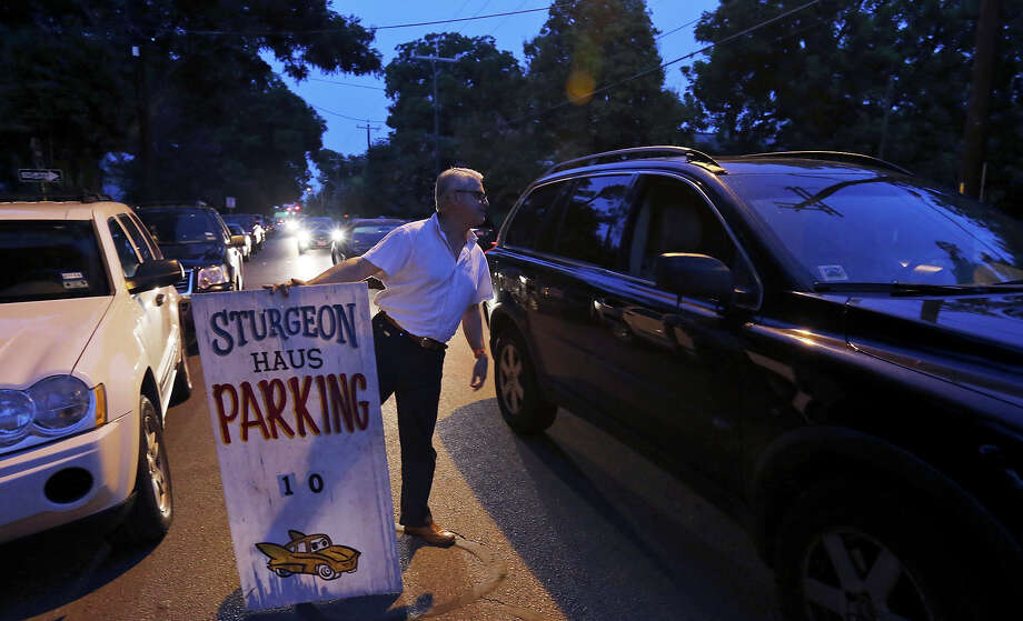 Tony Escobedo, who helps out the owner of Sturgeon Haus, talks with a motorist about First Friday parking in the Southtown area. Photo: Edward A. Ornelas /San Antonio Express-News / © 2015 San Antonio Express-News