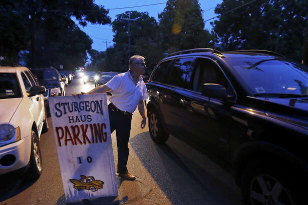 Tony Escobedo, who helps out the owner of Sturgeon Haus, talks with a motorist about First Friday parking in the Southtown area.