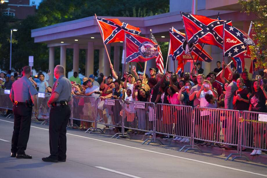 People wave Confederate flags outside the hotel that President Barack Obama is staying the night, on Wednesday, July 15, 2015, in Oklahoma City. Obama is traveling in Oklahoma to visit El Reno Federal Correctional Institution. (AP Photo/Evan Vucci)