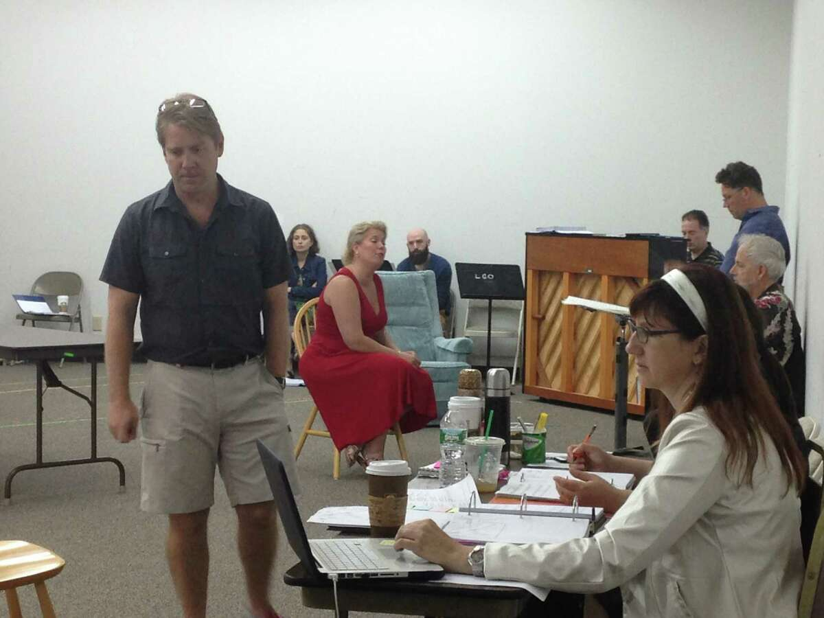 """Daniel Belcher, left, and Caroline Worra, seated in red, during a rehearsal for Saratoga Opera's """"The Long Walk"""" (photo by Amy Biancolli)"""